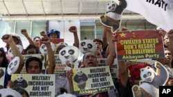 Protesters shout slogans during a rally outside the Chinese Consulate at financial district of Makati city, east of Manila, Philippines to protest alleged Chinese government's alleged military incursions into the disputed Spratly group of islands in the S