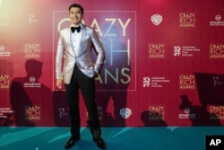 """Actor Henry Golding poses as he arrives for the red carpet screening of the movie """"Crazy Rich Asians,"""" Aug. 21, 2018, in Singapore."""