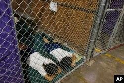 Dos mujeres detenidas duermen en una celda en el Centro de Admisión de Aduanas y Protección Fronteriza de Nogales, Arizona, donde los niños inmigrantes ilegales están separados por grupos de edad y sexo. Cientos de niños centroamericanos en su mayoría están siendo procesados y retenidos en en el Centro de Nogales.