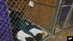 Tư liệu - Trong bức hình chụp vào tháng năm 2014, hai người nữ nằm ngủ trong buồng giam trong khi trẻ em được tách riêng theo nhóm tuổi và giới tính, tại một trung tâm giam giữ di trú ở Nogales, bang Arizona.