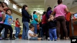 Di dân nhập cư Mỹ bất hợp pháp xếp hàng lấy vé tại một trạm xe buýt sau khi được thả ra từ một cơ sở xử lý của Cục Hải quan và Biên phòng Hoa Kỳ ở McAllen, Texas, 20/6/2014.