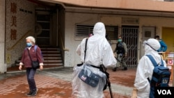 外國傳媒攝影隊穿上全套保護衣到爆發武漢肺炎疫情的康美樓拍攝。(美國之音 湯惠芸拍攝)