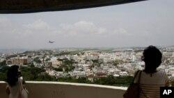 일본 오키나와 후텐마에 있는 미 해병 항공기지 방면을 바라보고 있는 주민들. (자료사진)
