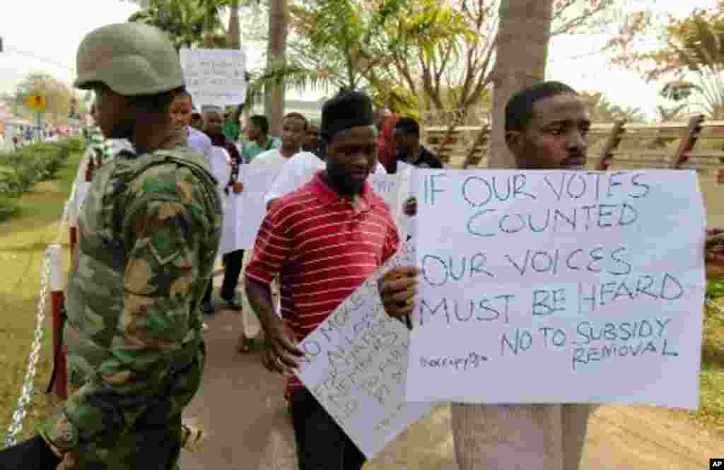 Protesters walk past a soldier standing guard during a rally against fuel subsidy removal in Nigeria's capital Abuja, January 6, 2012. Nigerians angered by the government's decision to remove fuel subsidies protested in the capital on Friday, showing dete