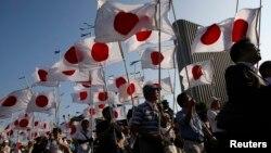 """Các thành viên của phong trào dân tộc """"Ganbare Nippon"""" diễu hành đến đền thờ Yasukuni với quốc kỳ Nhật Bản. Đền Yasukuni thờ gần 2,5 triệu người chết trong chiến tranh, trong đó có 14 tội phạm chiến tranh đã bị kết án vì các hành động gây ra trong Thế Chiến II."""