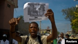 FILE - A demonstrator participates in a Nov. 2012 anti-government march shouts while carrying a flier with images of Clifford Brandt, son of a wealthy Haitian businessman who heads an alleged kidnapping ring, and Olivier Martelly, son of Haiti's president.