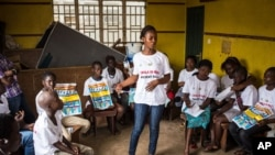 FILE - A charity worker, center, from the GOAL Ireland humanitarian agency, educates children on how to prevent and identify the Ebola virus in their communities at Freetown, Sierra Leone.