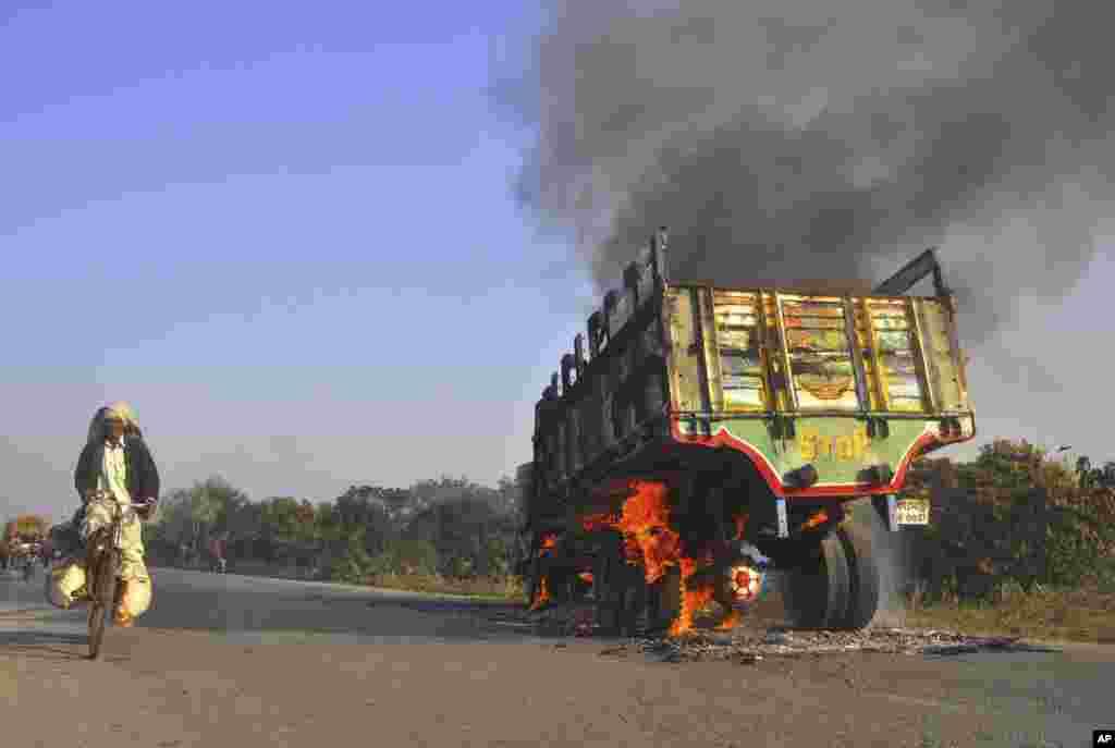 A man rides past a truck set on fire during a strike called by Jamaat-e-Islami in Rajshahi, Bangladesh, Feb. 28, 2013.