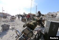 Men loot goods in al-Shadadi town, Hasaka countryside, Syria, Feb. 26, 2016.