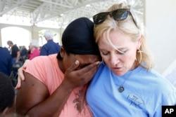ນາງ April Moore ພົນລະເມືອງ Gulfport (ຊ້າຍ) ຮ້ອງໄຫ້ ຫຼັງຈາກທີ່ຂອບອົກຂອບໃນນາງ Anne Warren ຂອງໂບດ Gulf Coast Blessing ສຳຫັລບການໄຫວ້ພາວະນາຈາກກຸ່ມສຶກສາຄຳພີ ພາຍຫຼັງພິທີ ລະນຶກເຖິງວັນຄົບຮອບ 10 ປີ ຂອງລົມພາຍຸ Katrina ໃນເມືອງ Gulfport, ລັດ Mississippi, ວັນທີ 29 ສິງຫາ 2015.