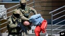 Polisi Bosnia mengawal pria yang diduga terkait dengan ekstremis-ekstremis Islamis, di kota Banja Luka, Bosnia (8/5). (AP/Radivoje Pavicic)