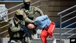 FILE - Bosnian Serb police escort a man suspected of links to Islamic extremists to court in the town of Banja Luka, Bosnia, May 8, 2015.