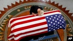 Cindy McCain, vợ Thượng nghị sĩ John McCain, tựa đầu vào linh cữu của ông trong một buổi lễ tưởng niệm tại tòa nhà lập pháp bang Arizona ở Phoenix, ngày 29 tháng 8, 2018.