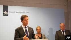 Perdana Menteri Belanda Mark Rutte, kiri, dalam konferensi pers menjelaskan pemerintah Belanda menunda pengiriman tentara bersenjata untuk menjaga lokasi jatuhnya pesawat MH17.