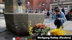 Un hombre coloca una vela en el lugar donde una camioneta embistió contra personas que estaban sentadas en las afueras de un popular restaurante en el centro de la ciudad vieja de Muenster, Alemania, 8 de abril, 2018. REUTERS/Wolfgang Rattay