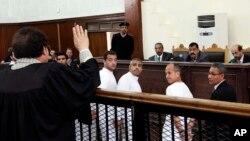 ຜູ້ຜະລິດລາຍການ ພະແນກພາສາອັງກິດ ຂອງອົງການຂ່າວ Al-Jazerra Baher Mohamed (ກາງ) ຜູ້ຮັກສາການຕາງໜ້າຫົວໜ້າຫ້ອງການໃນ Cairo Mohammed Fahmy (ກາງ) ຊາວອີຈິບ ສັນຊາດການາດາ ແລະ ຜູ້ສື່ຂ່າວ Peter Greste (ຂວາ) ປະກົດຕົວຢູ່ສານໃນອີຈິບ ພ້ອມກັບຈຳເລີຍອີກຫຼາຍຄົນ.