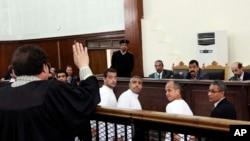 半岛电视台记者澳大利亚人格雷斯特(右二),埃及裔加拿大人莫哈米德•法赫米(中)和埃及人半岛电视台英语制片巴赫尔•莫哈米德(左中)在埃及法庭受审。(资料照片)