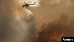 Sebuah helikopter menyiramkan air di kebakaran hutan yang dipicu angin kencang di California, 9 Oktober 2017.