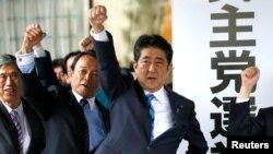 PM Jepang Shinzo Abe (tiga dari kiri) dan anggota parlemen partainya mengangkat kepalan tangan mereka ke atas sambil mengucapkan kebulatan tekad untuk memenangkan pemilihan majelis rendah mendatang, di markas partai mereka di Tokyo, Jepang, 28 September 2017.