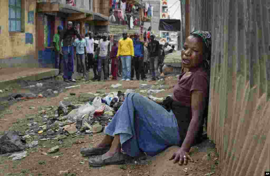 A relative wails on the floor of an alleyway near the body of a man who had been shot in the head as the angry crowd shouts at the police, in the Mathare slum of Nairobi, Kenya. Kenya's election took an ominous turn as violent protests erupted in the capital.