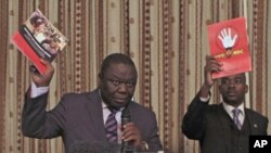 Zimbabwe Prime Minister and Movement For Democratic Change (MDC) leader Morgan Tsvangirai (L) and National Organising Secretary Nelson Chamisa present a booklet at the launch of Conditions for a Sustainable Election in Zimbabwe (COSEZ) in Harare, March 8