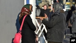 """Two women talk in the so called """"Mahgreb Quarter"""" in Duesseldorf, Germany, Jan. 19, 2016. Germany is still taking in around 2,000 refugees a day, but it is now denying entry to about 200 others daily at its borders, the country's interior minister said on Jan. 24, 2016."""