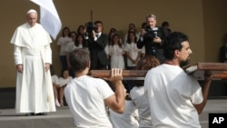 Paus Fransiskus (kiri) menunggu beberapa pemuda yang membawa kayu salib di Turin, Italia hari Minggu (21/6).