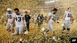 Los jugadores de Oregón salen del campo en medio de una lluvia de confetí luego que Ohio State los derrotara en la final universitaria jugada en Arlington, Texas.