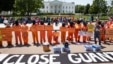 Activists wearing orange jumpsuits mark the 100th day of prisoners