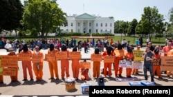 Para aktivis dengan mengenakan pakaian tahanan, menuntut penutupan pusat tahanan AS di Guantanamo, Kuba, dalam aksi protes di depan Gedung Putih (17/5).