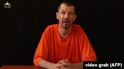 An image taken from a video released by the Islamic State (IS) group through Al-Furqan Media via YouTube allegedly shows British freelance photojournalist, John Cantlie, at an undisclosed location in which he says he is being held captive, Sept. 18, 2014.