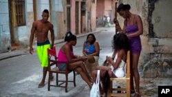 Lisandra, una peluquera, trabaja en las extensiones de una mujer, mientras otras esperan su turno en la vieja Habana.
