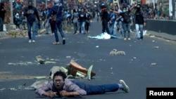 Seorang peserta demo terjatuh di jalan saat bentrokan antara pengunjuk rasa mahasiswa dengan polisi di Makassar, Sulawesi Selatan, 24 September 2019. (Foto: Reuters)