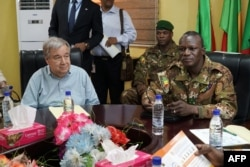 FILE - U.N. Secretary-General Antonio Guterres, left, meets with Malian Army General Didier Dacko, Force Commander of the G5 Sahel, in Mali, May 29, 2018.