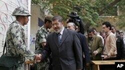 ໂຄສົກຂອງກຸ່ມພະລາດອນພາບມຸສລິມ ທ່ານ Mohammed Morsi ຈັບມືກັບທະຫານຄົນນຶ່ງ ໃນມື້ທຳອິດຂອງ ການເລືອກຕັ້ງສະພາແຫ່ງຊາດ ທີ່ນະຄອນຫຼວງໄຄໂຣ (28 ພະຈິກ 2011)