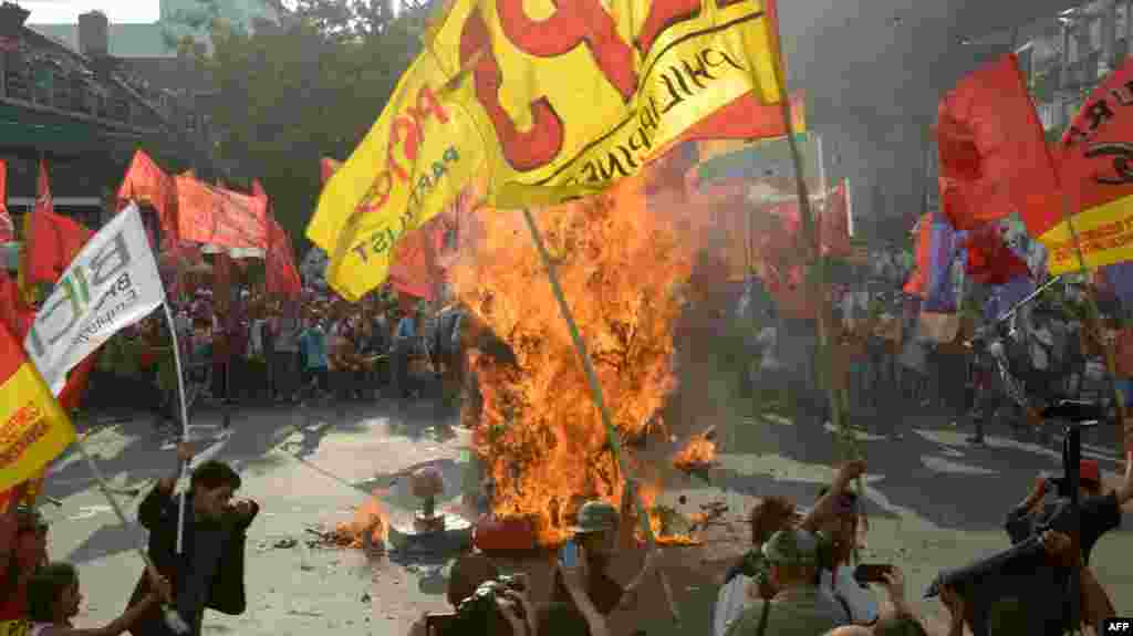 Protesters set fire to an effigy of Philippine President Benigno Aquino during a May Day rally near the presidential palace in Manila.