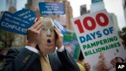 """Un manifestante lleva una máscara de Donald Trump durante una protesta y marcha del """"100 Días de Falla"""", el sábado 29 de abril de 2017, en Nueva York."""