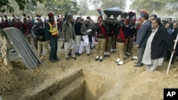 Pakistani police carry the coffin of Punjab Gov. Salman Taseer, shortly before burial in a cemetary in Lahore, Pakistan, Jan. 5, 2011.