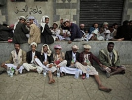Yemeni anti-government protesters rest sitting on a sidewalk chewing Qat during clashes between the factions in Sana'a, March 13, 2011.
