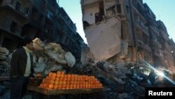 A man sells oranges along a damaged street in the al-Shaar area in Aleppo, Dec. 27, 2013.