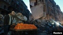Ulični prodavac pomorandži na ulici u teško oštećenom delu Alepa