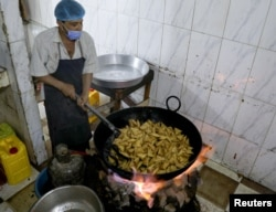 Seorang juru masak tengah menggoreng sambusa di sebuah restoran di Sanaa, Yaman, pada bulan suci Ramadan, 15 April 2021. (REUTERS / Khaled Abdullah)