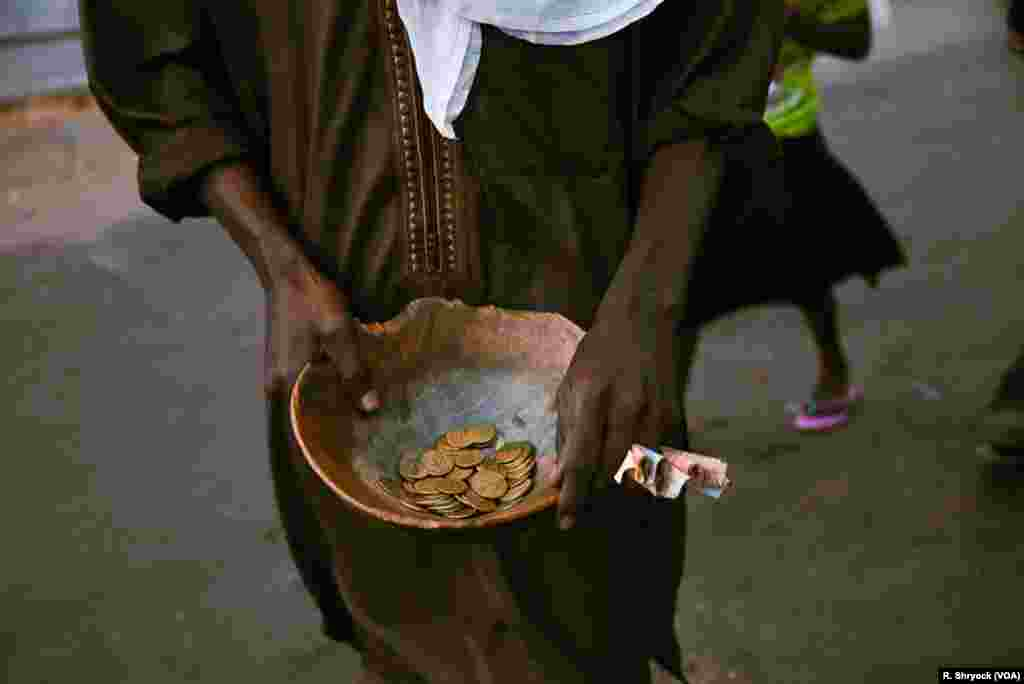 A man takes donations to help with the costs of making the Ndogou meal, which they then share with anyone who passes by as the sun sets and it's time to break the Ramadan fast each night in Dakar, Senegal.