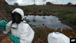 FILE - Waste removal experts work to remove hazardous black sludge from a garbage dump in Abidjan, Ivory Coast.
