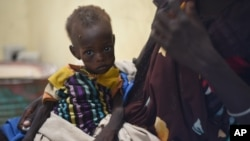 Nyagoah Taka Gatluak, a severely malnourished 1-year-old child, sits on her mother's lap in the Doctors Without Borders clinic in Leer, South Sudan, Dec. 15, 2015 — the two-year anniversary of the beginning of the country's civil war.