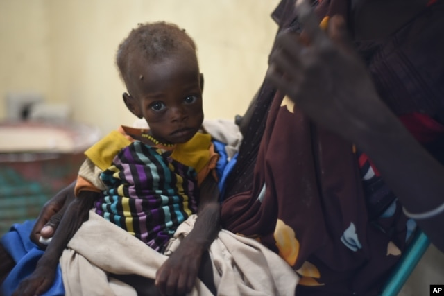 FILE - Nyagoah Taka Gatluak, a severely malnourished 1-year-old child, sits on her mother's lap in the Doctors Without Borders clinic in Leer town, South Sudan, Dec. 15, 2015 — the two-year anniversary of the beginning of South Sudan's civil war.