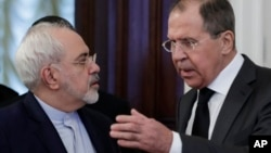 FILE - Russian Foreign Minister Sergei Lavrov, right, speaks to Iranian Foreign Minister Mohammad Javad Zarif as they enter a hall for the talks in Moscow, Russia, Dec. 20, 2016. In the past few years an alliance — at times shaky — between Moscow and Tehran has developed.