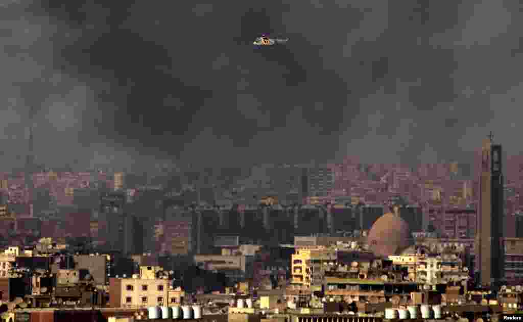 A military helicopter among clouds of smoke in Cairo, July 26, 2013.