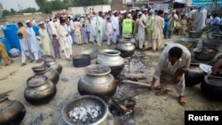 FILE - A Pakistani non-governmental humanitarian organization volunteer (front) adjusts a cooking fire as locals line up to receive meals in Nowshera, in Pakistan's northwest Khyber-Pakhtunkhwa Province, Sept. 10, 2010. Foreign-funded local organizations in northwestern Pakistan provide humanitarian and emergency assistance, including health, education, and food distribution, to more than two million people who have been displaced by ongoing Pakistani military operations against militant groups.