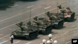 FILE - A Chinese man stands alone to block a line of tanks heading east on Beijing's Cangan Blvd. in Tiananmen Square in Beijing on June 5, 1989.
